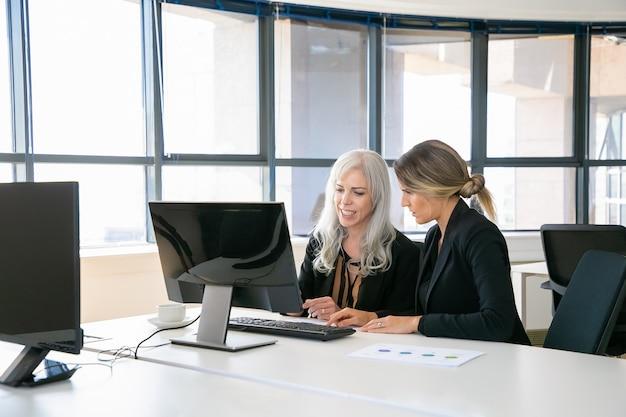 紙の図の近くのコンピューターを使用して、一緒に職場に座っている女性の同僚。ビジネスコミュニケーションまたはメンターシップの概念 無料写真