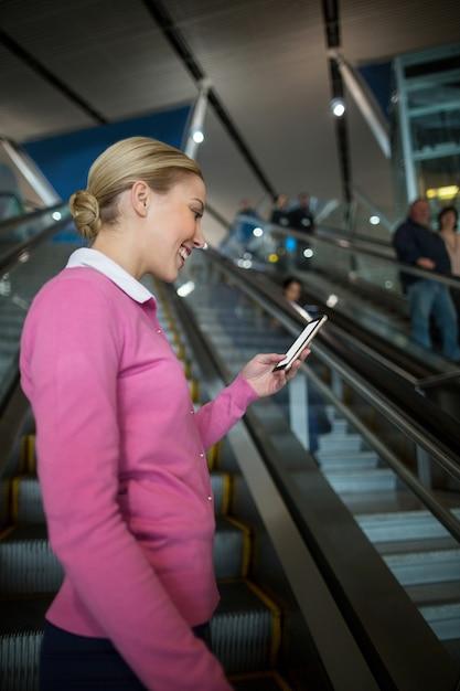 Женский пригородный поезд с помощью мобильного телефона на эскалаторе Бесплатные Фотографии