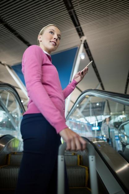 Пассажирка с багажом, используя мобильный телефон на эскалаторе Бесплатные Фотографии