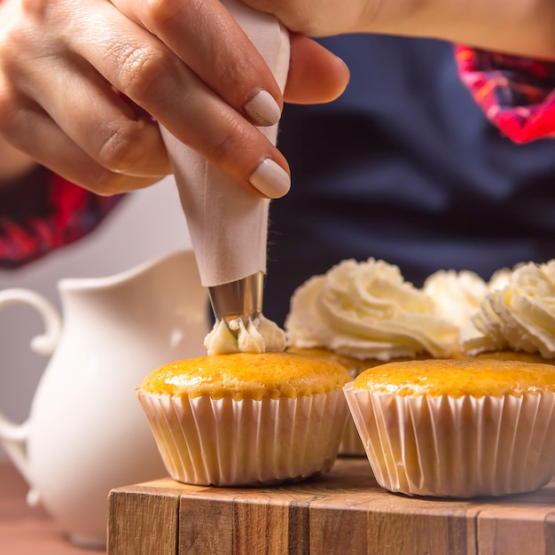 Female confectioner in a blue apron and a plaid red shirt applies cream to cupcakes Premium Photo