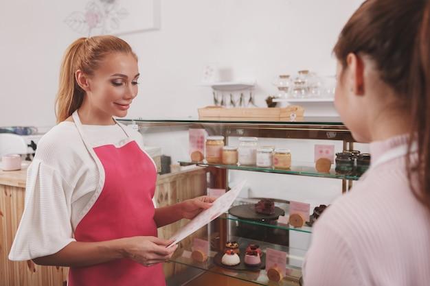 Женщина-кондитер разговаривает с коллегой, работающей в магазине сырых веганских кондитерских изделий Premium Фотографии