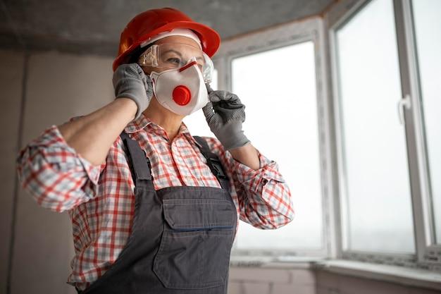 フェイスマスクを身に着けているヘルメットとヘッドフォンを持つ女性の建設労働者 無料写真