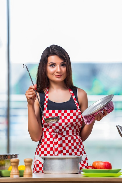 Female cook preparing soup in brightly lit kitchen Premium Photo