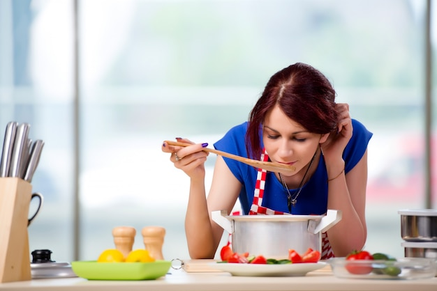 Female cook preparing soup in brightly lit kitchen Premium Photo