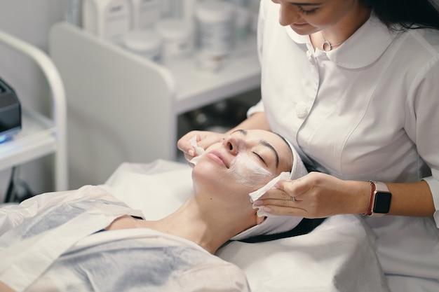 아름다운 할에 얼굴 치료를하는 여성 미용사 무료 사진