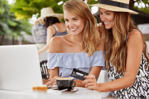 Female couple in love make shopping online, rejoice new purchases, have happy looks in laptop computer. online payment or e commerce Free Photo
