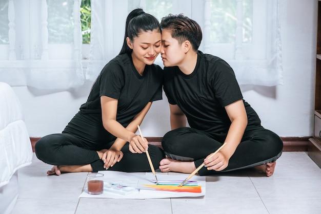 女性のカップルは、紙に描き、ペイントします。 無料写真