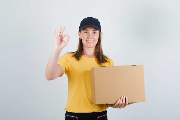 Female courier holding cardboard box with ok sign in t-shirt, pants, cap and looking glad Free Photo