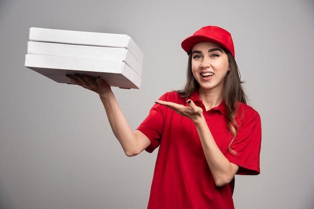 灰色の壁にピザの箱を保持している女性の宅配便。 無料写真