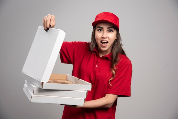 灰色の壁に空のピザボックスを保持している赤い制服を着た女性の宅配便。 無料写真