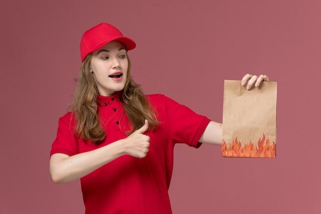 ピンクの制服労働者サービスの配達に紙の食品パッケージを保持している赤い制服の女性の宅配便 無料写真