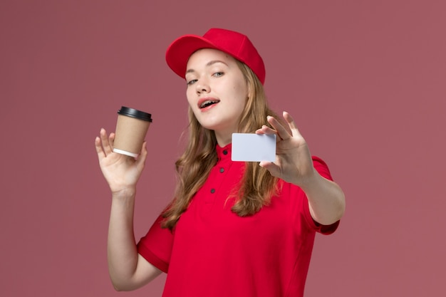 Female courier in red uniform holding coffee cup along with white card on light pink, job uniform worker service delivery Free Photo