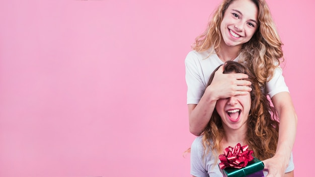 Female covering her friend's eyes giving gift box against pink background Free Photo