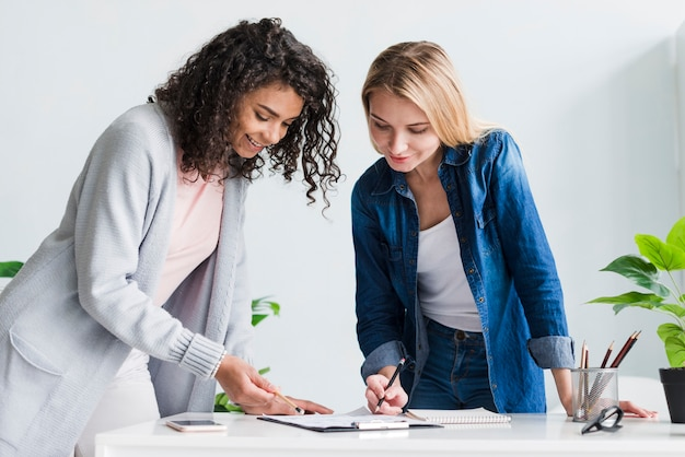 Female coworkers leaning over desk discussing project Free Photo