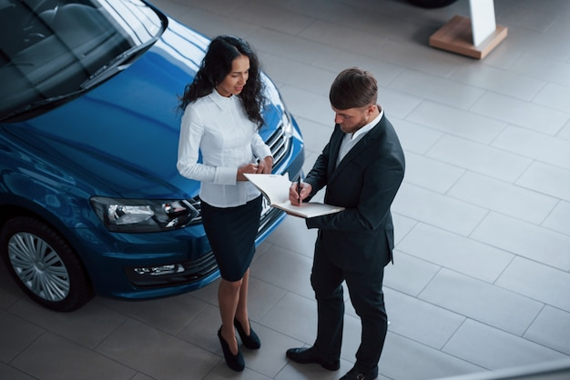 Cliente femminile e uomo d'affari barbuto elegante moderno nel salone dell'automobile Foto Gratuite