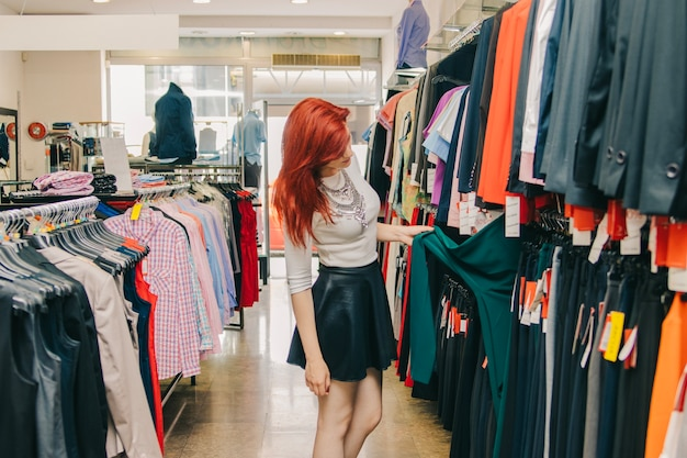 female customer picking clothes in shop photo  free download