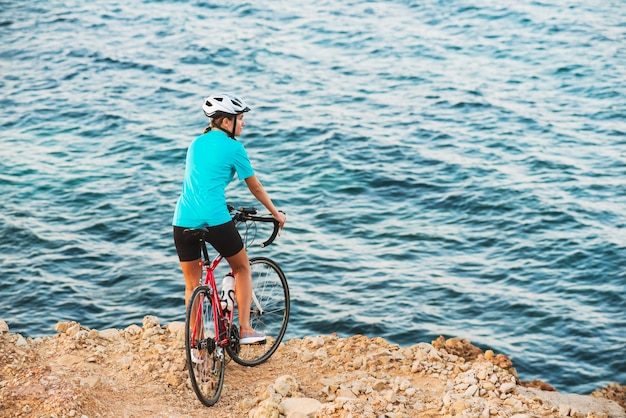 Female cyclist standing on a hill and looking at sea Premium Photo