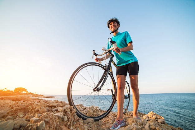 Female cyclist standing on a rock and looking at sea Premium Photo