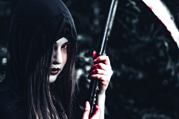 Female demon witch with bloody reaper standing in front of mystery forest Premium Photo
