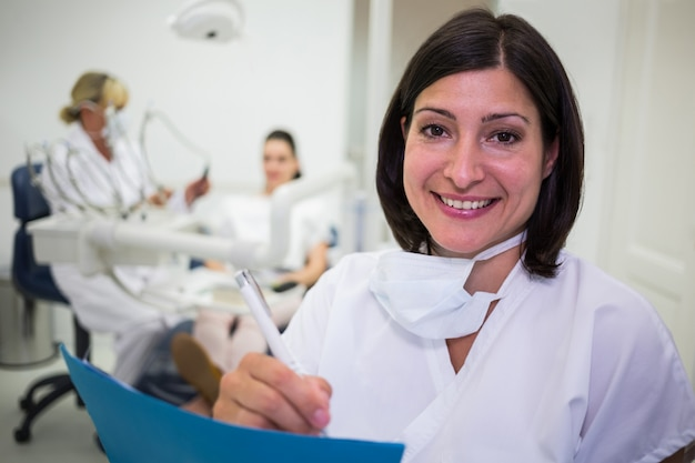 Female dentist writing report in dental clinic Free Photo