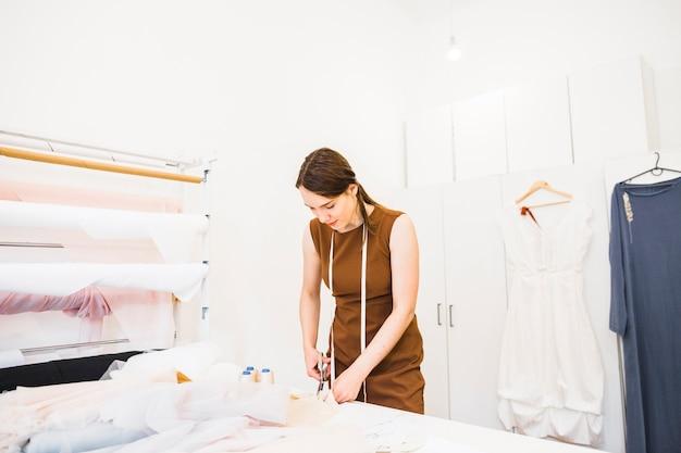 Female designer cutting fabric with scissors Free Photo