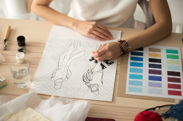 Female designer hands painting embroidery pattern scheme on fashion sketch Free Photo