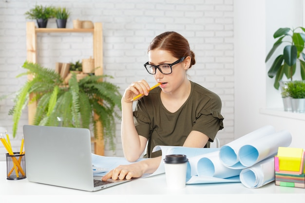 Female designer in office working on architects project Premium Photo