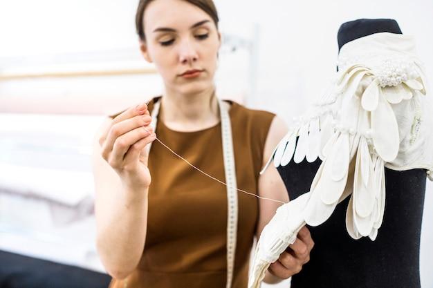 Female designer sewing dress with needle Free Photo