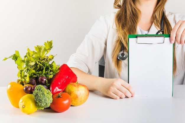 Female dietician's hand holding blank clipboard with healthy food on desk Free Photo