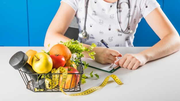 Female dietician's hand near healthy fruits and dumbbells in tray Free Photo