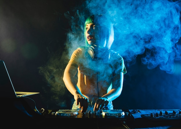 Female dj in club covered by colorful smoke Free Photo