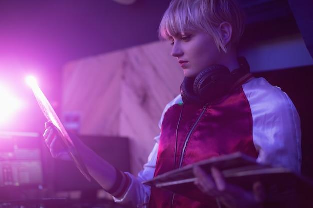 Женский ди-джей держит пластинку винилового диска в баре Бесплатные Фотографии
