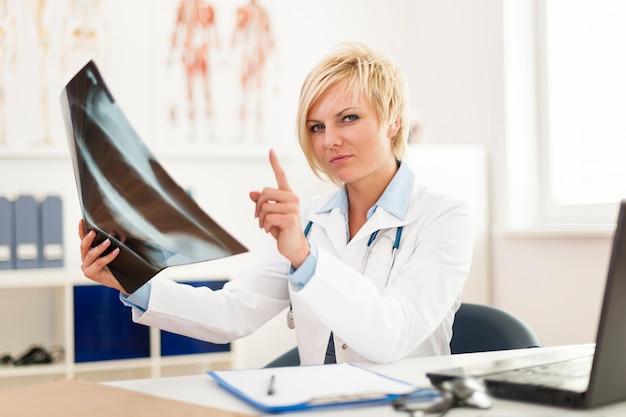 Medico femminile che controlla l'immagine dei raggi x Foto Gratuite