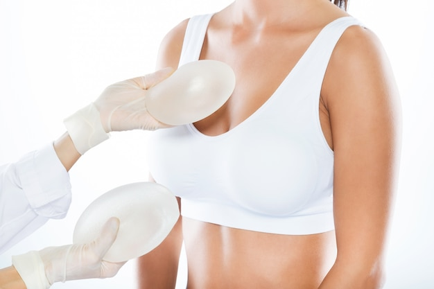 Female doctor choosing mammary prosthesis with her patient over white background. Free Photo