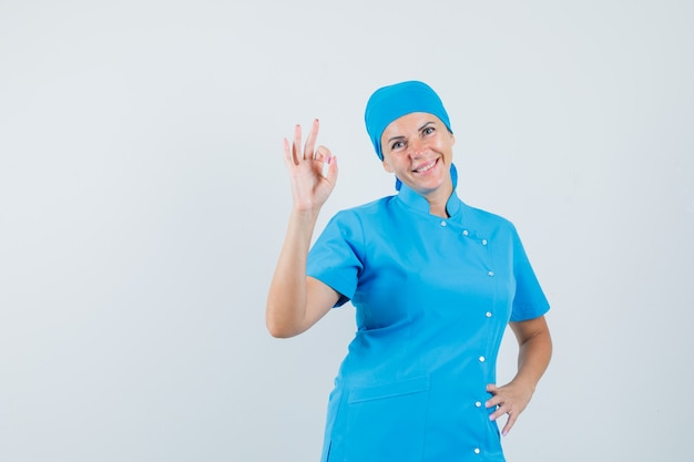 Женщина-врач делает хорошо жест в синей форме и выглядит уверенно, вид спереди. Бесплатные Фотографии
