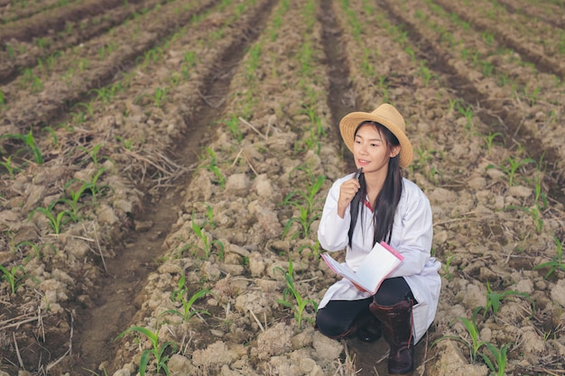 The female doctor examines soil with a modern concept book. Free Photo