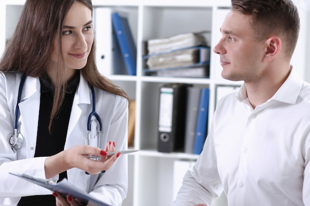 Female doctor hand hold silver pen and showing pad. physical agreement form signature disease prevention ward round reception consent contract sign prescribe remedy healthy lifestyle concept Premium Photo
