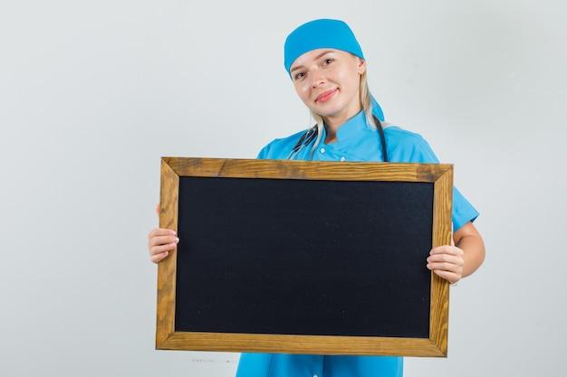 Medico femminile che tiene lavagna e sorridente in uniforme blu Foto Gratuite