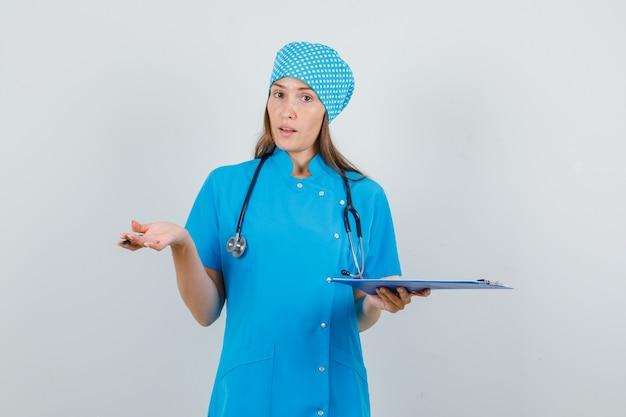 青い制服を着てクリップボードとペンを保持し、混乱しているように見える女性医師。正面図。 無料写真