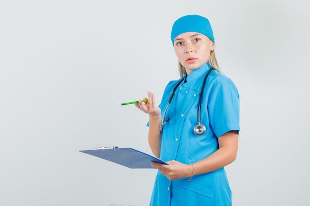 青い制服を着てクリップボードと鉛筆を持って混乱しているように見える女性医師 無料写真