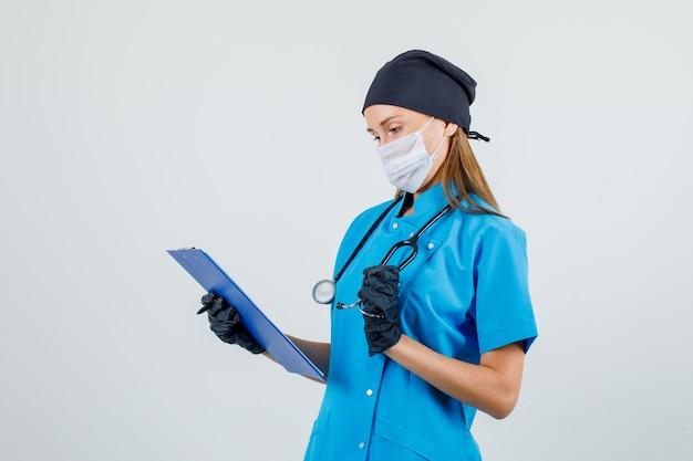 Medico femminile che tiene appunti e stetoscopio in uniforme, guanti, maschera e sembra occupato. Foto Gratuite