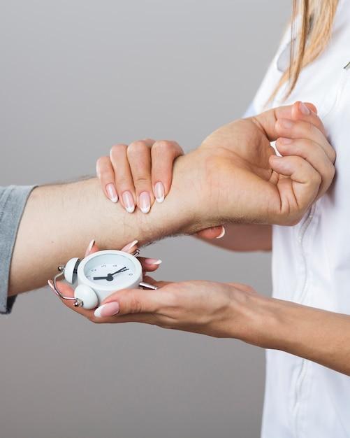 Medico femminile che tiene un orologio e una mano paziente Foto Gratuite