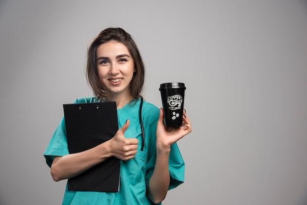コーヒーカップとクリップボードを保持している女性医師。 無料写真