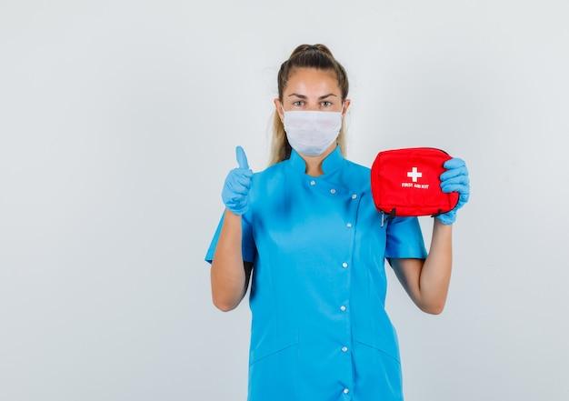 Medico femminile che tiene kit di pronto soccorso con il pollice in su in uniforme blu Foto Gratuite
