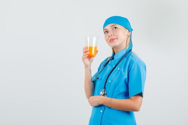 Medico femminile che tiene un bicchiere di succo mentre cerca in uniforme blu e sembra allegro Foto Gratuite