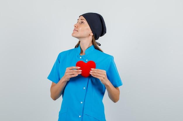 赤いハートを保持し、青い制服、黒い帽子の正面図で横を向いている女性医師。 無料写真