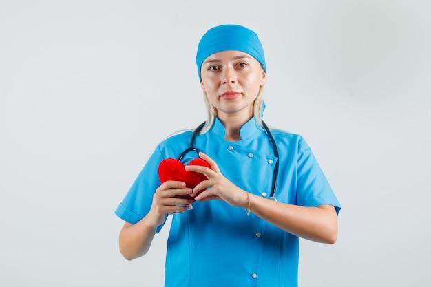 赤いハートを保持し、青い制服を着て笑っている女医師 無料写真