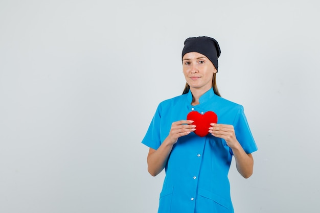 Female doctor holding red heart and smiling in blue uniform, black hat Free Photo