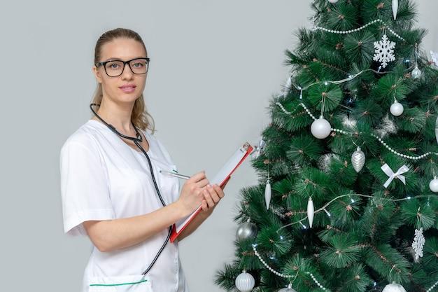 女性医師は、クリスマスツリーの背景にクリップボードを保持しています。病院で予約する Premium写真