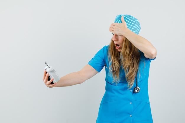 目覚まし時計を見て興奮している青い制服を着た女性医師 無料写真
